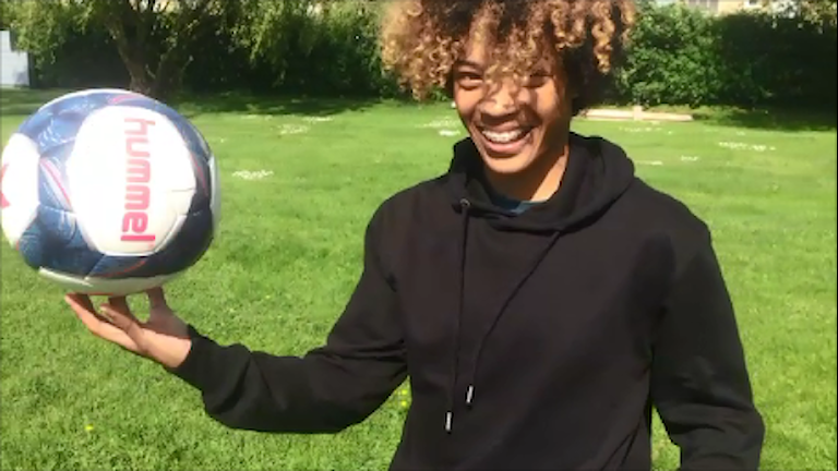 Fotbollsspelaren Evelina Duljan skrattar med en boll i handen.