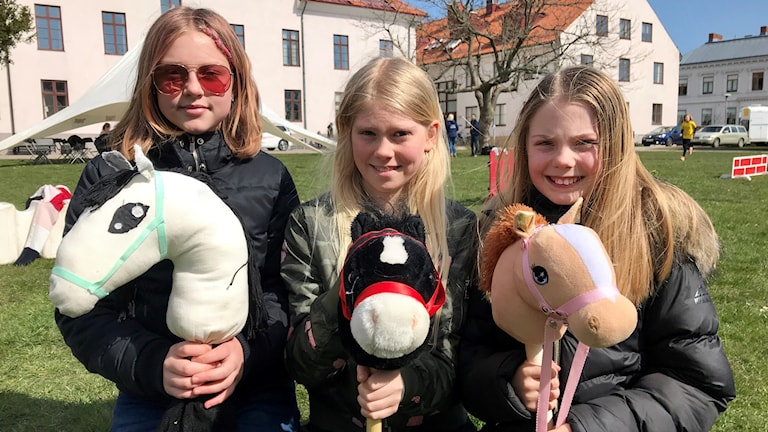 Tre flickor med käpphästar