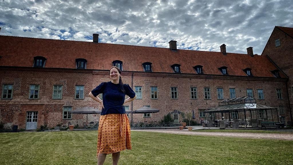 Kvinna som står på en gräsmatta, framför ett slott.