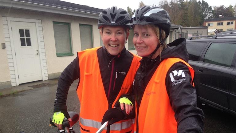 Två kvinnor med cykelhjälmar och reflexvästar.