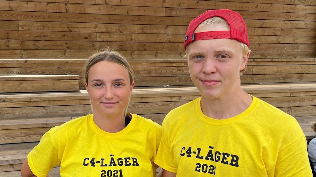 Ung tjej och ung kille i gula tröjor som det står c4-läger 2021 på. Båda står framför trätrappor och ler in i kameran
