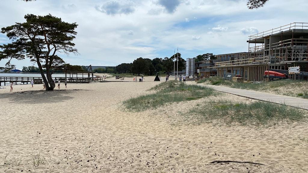 Bild på stranden i Åhus, en solig sommardag med lite moln på himlen. Till vänster på bilden syns en byggnad som håller på att byggas.