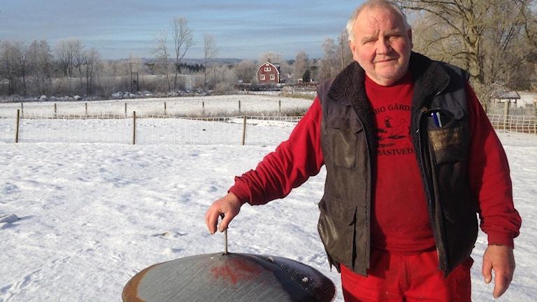Fågeluppfödaren Jan Radden vid en av sina foderautomater. Foto: Adam Bergsten/Sveriges Radio