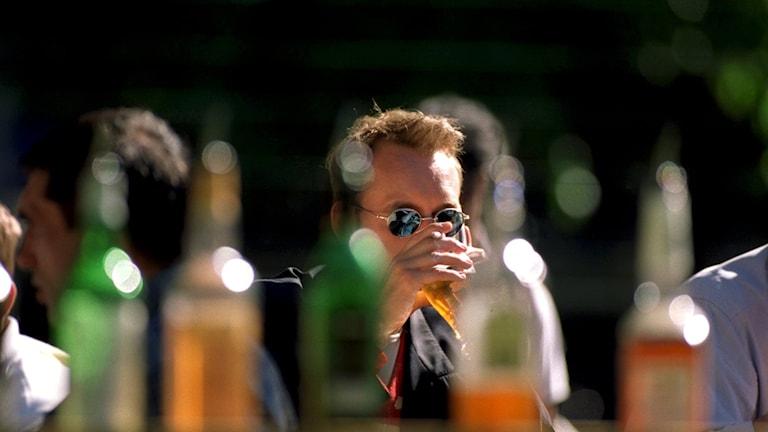 Ölflaksor i förgrunden och en man med solglasögon i skärpa som dricker ett glas med öl.
