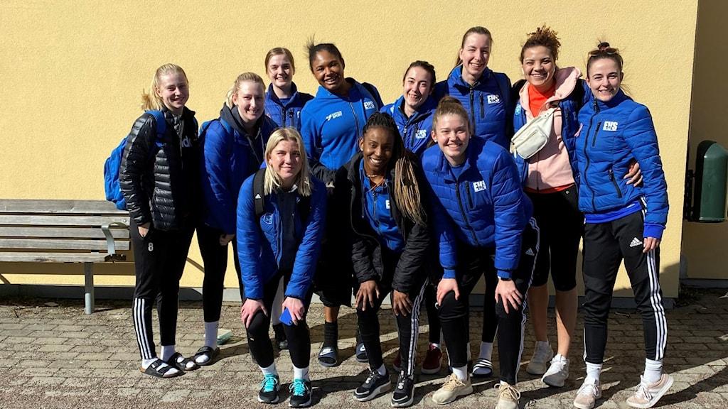 Volleyboll-lag med damer som står i gruppbild utomhus.