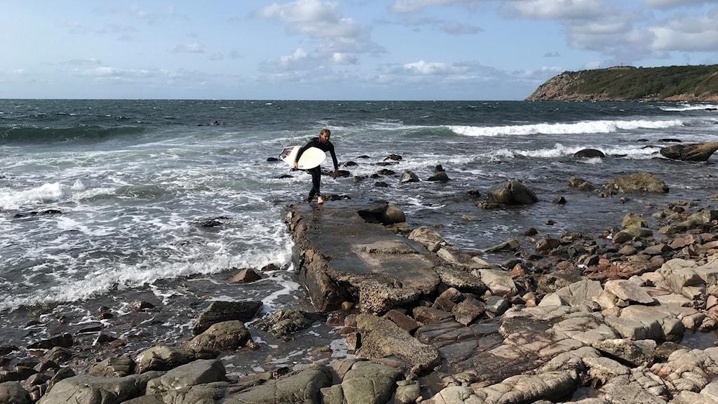En person i våtdräkt kommer upp hur havet med surfbräda under armen.  Hav och berg i bakgrunden. På platsen planeras en ny badbrygga.