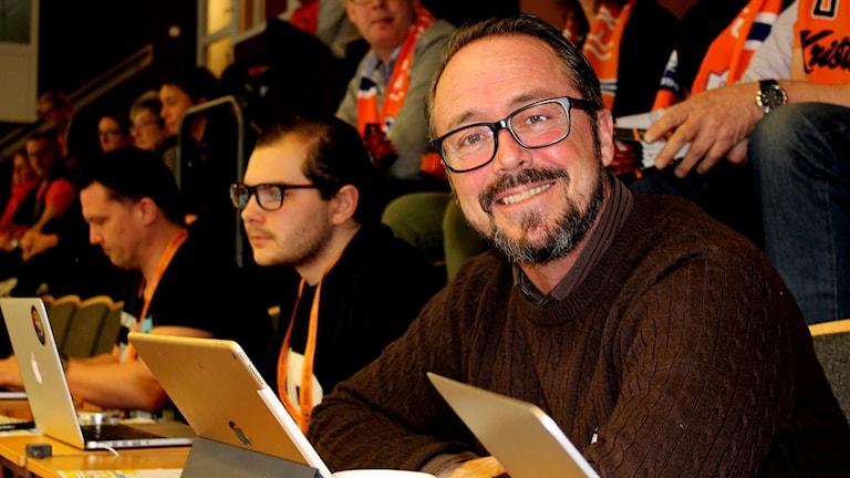 Man med glasögon och skägg som ler mot kameran.