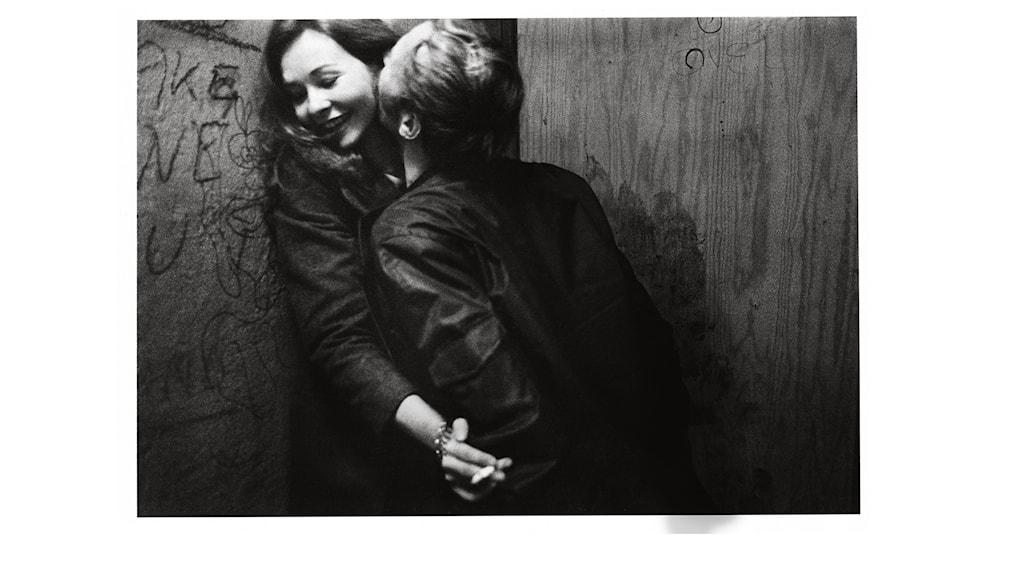 Kvinna och man som hånglar mot en vägg