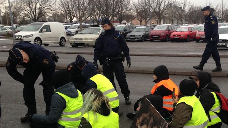 Demonstranter sitter ner och polis pratar med dem.