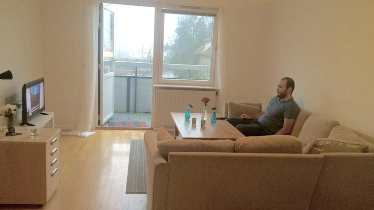 Ett vardagsrum där det sitter en en man och ser på tv.