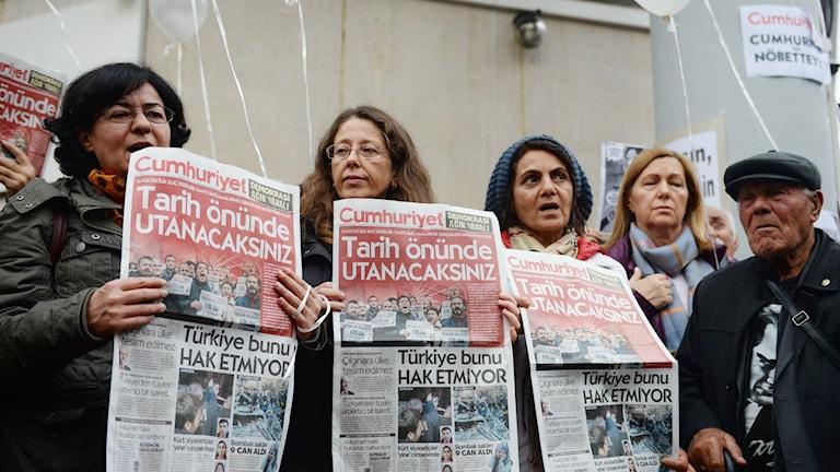 """Demonstranter håller upp den senaste utgåvan av den turkiska dagstidningen """"Cumhuriyet"""" under en demonstration utanför tidningens huvudkontor i Istanbul, Turkiet."""