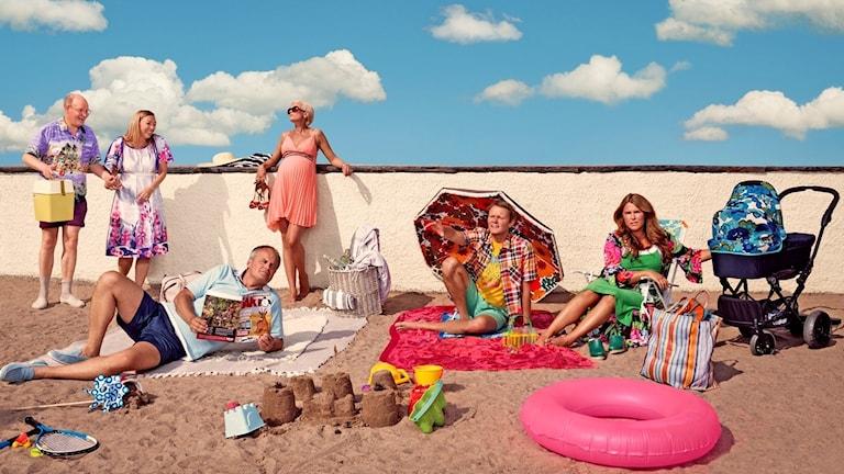Personer ligger och står på en sandstrand med parasoll, sandslott, barnvagn och badring.
