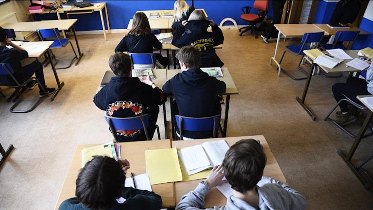 Elever sitter vid sina bänkar i ett klassrum.