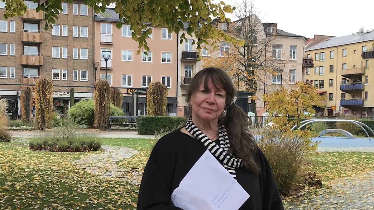 En kvinna står i en park och håller i ett dokument.