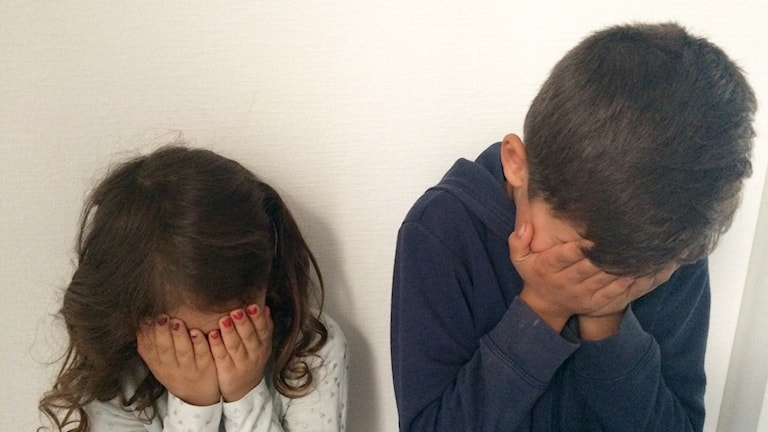 Två barn, en tjej och kille gömmer ansiktet i sina händer.