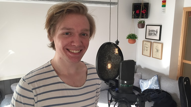 Ung blond man tittar leende in i kameran. Han har en mikrofon framför sig.