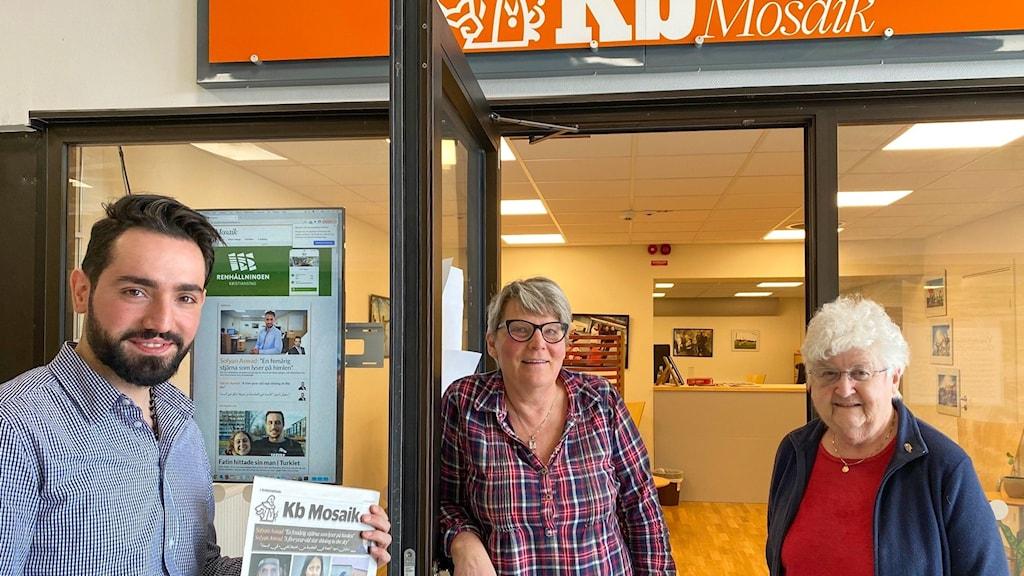 Tre medarbetare på KB Mosaik framför tidningens redaktion i Gamlegården: Sofyan Awad i smårutig blåvit skjorta,  redaktör Inga-Lill Bengtsson i skotskrutig rödblå skjorta och översättaren Moira Uggla i blå kofta och röd t-tröja.