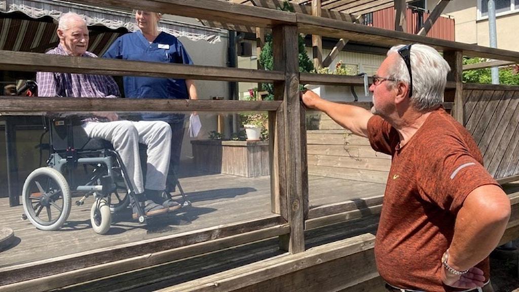Gert-Åke Persson får efter fyra månader till slut träffa sin vän, 95-årige Gunnar Cronsell, igen. Men det måste ske på några meters avstånd. Gruppchefen på äldreboendet Lindgården i Broby, är med under besöket. Foto: Karl Eckhardt/Sveriges Radio