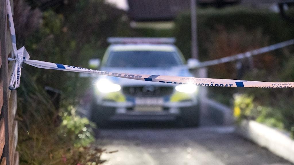 Bild på avspärrningsband med polisbild i bakgrunden.