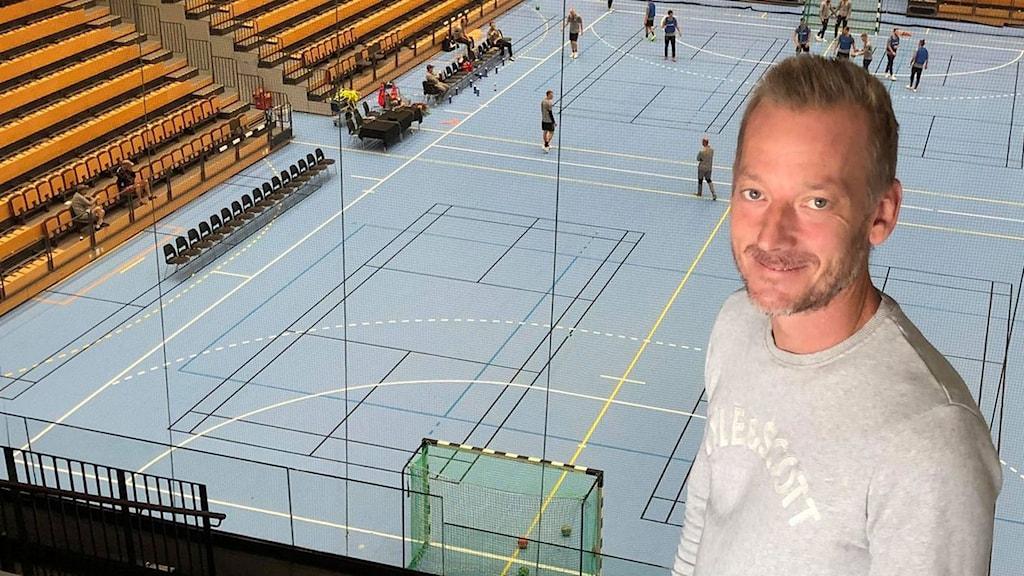 Henrik Fröberg som står i en restaurang med utsikt över handbollsplanen där det spelas handboll.