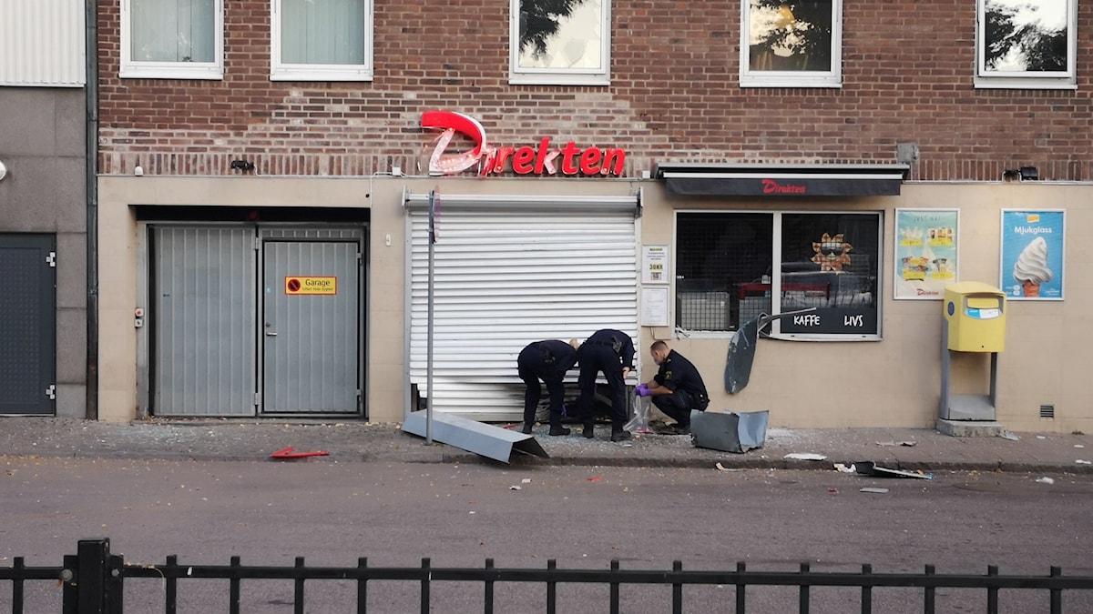 Poliser på gatan utanför sprängd butiksentré i Landskrona.