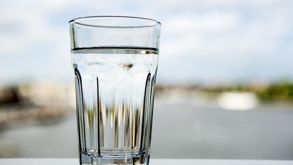 Ett vattenglas som står mot ljus bakgrund.
