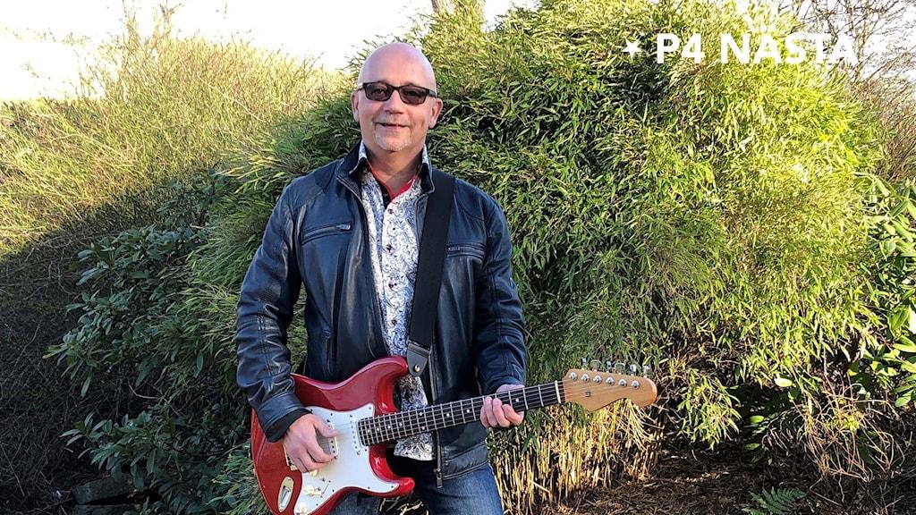 Man med gitarr i trädgård