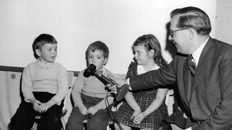 Svartvit bild med man som intervjuar barn