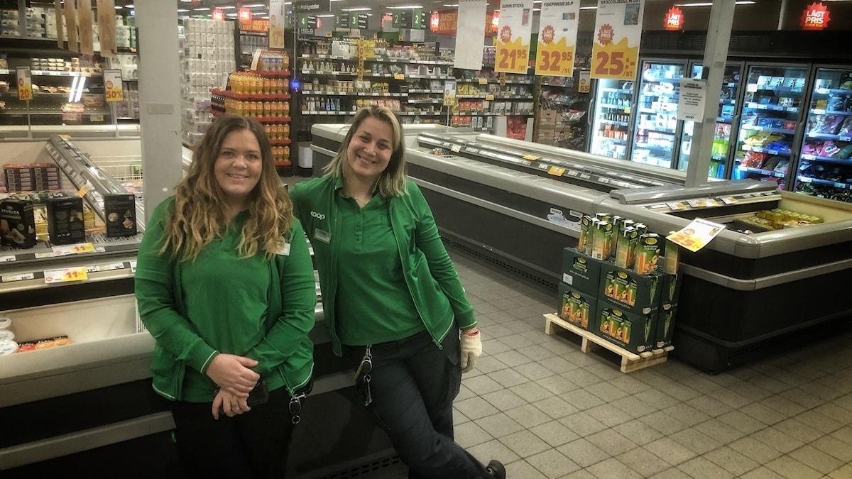 två tjejer framför frysdiskar i matvaruaffär