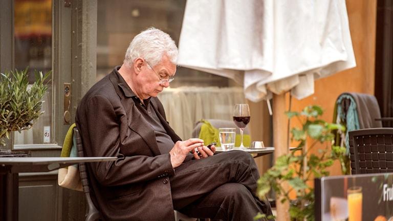Man med mobiltelefon på ett utomhuskafé.