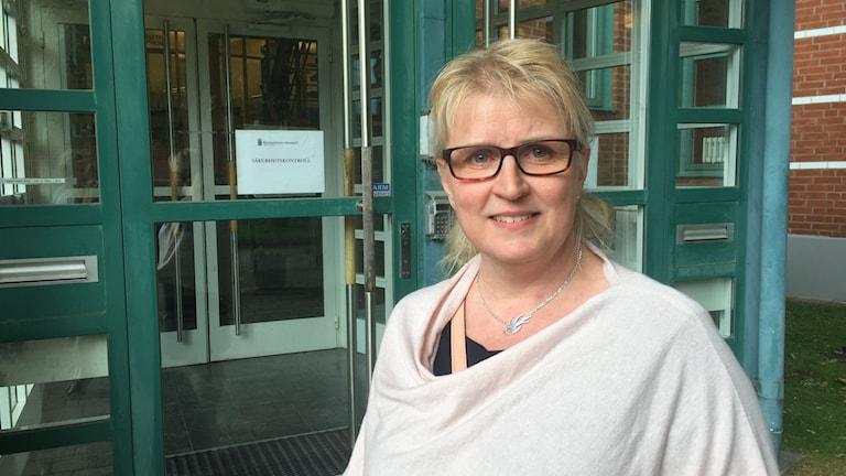 Kvinna med glasögon och blont uppsatt hår står framför en entré.