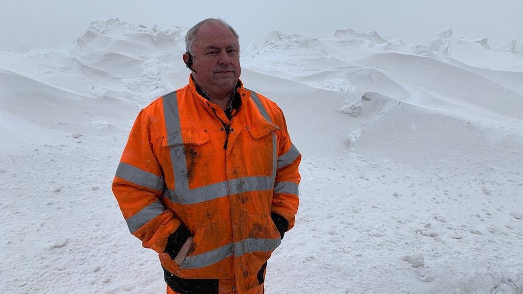 Man i orange overall bland snö