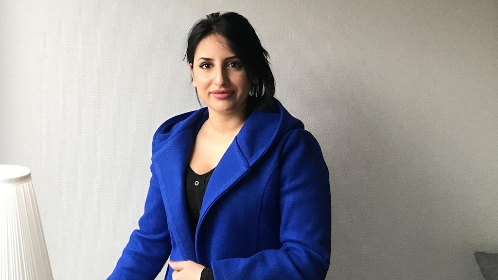 En tjej står i en blå jacka mot en vit vägg.