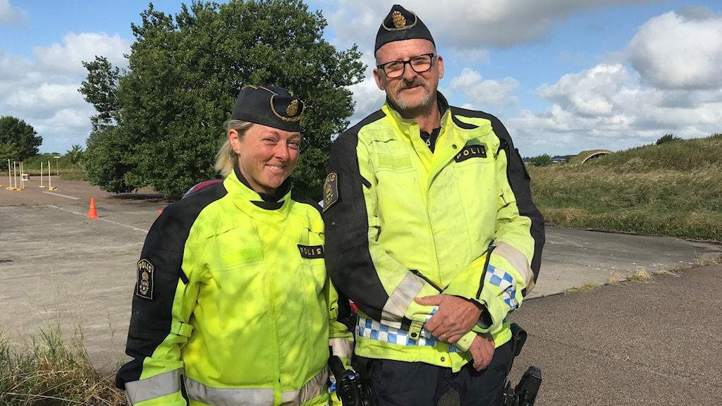 En kvinnlig och en manlig polis i gula reflexjackor vid en övningsbana för motorcyklar.