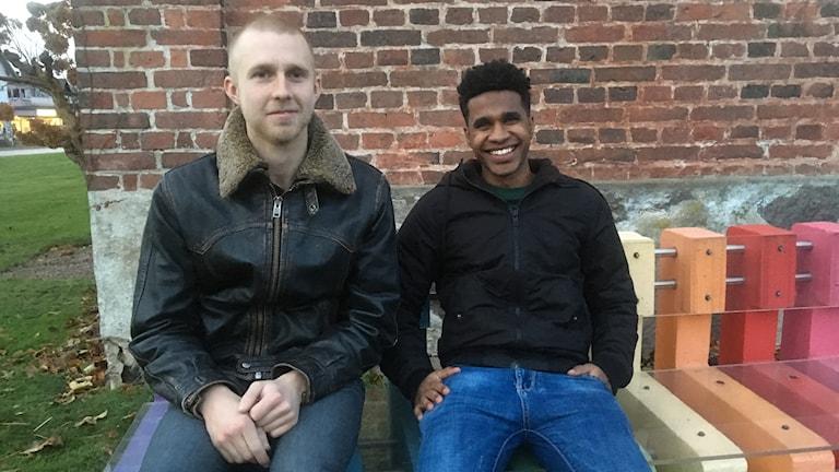 Två män sitter på en bänk och ler in i kameran