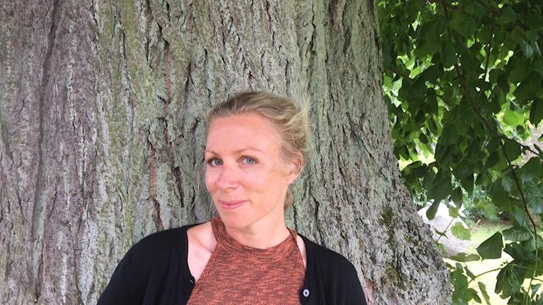 Blond kvinna som stor framför trädstam