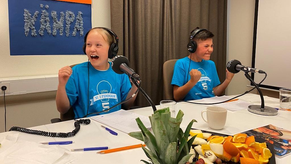 Två glada barn i blåa t-shirtar.