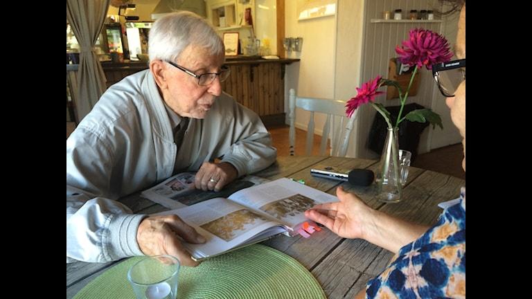 Sten Fält,94,  läser den årsgamla boken om Seskarö. Foto: Bertil Isaksson/SR