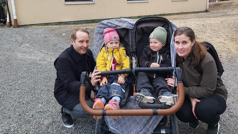 fyra personer två vuxna två barn som sitter i barnvagn