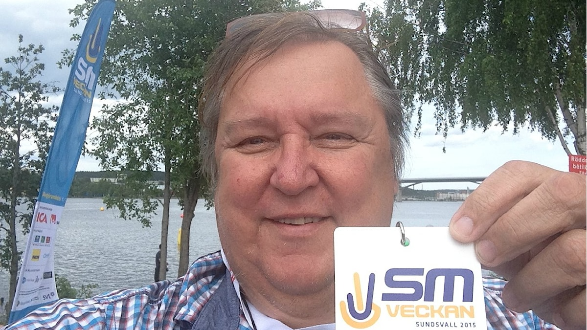 Erpo Heinolaisella on kädessään SM viikon lehdistökortti. Takana näkyy viikon tunnusviiri ja Sundsvallin uusi iso silta. Selfiefoto: Erpo Heinolainen SR Sisuradio
