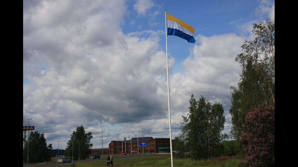 Meänmaan flagu, jossa raidat ylhäältä lueteltuna ovat keltainen, valkoinen ja sininen, liehuu pilvipoutaisessa säässä. foto: Hannele Kenttä SR Sisuradio