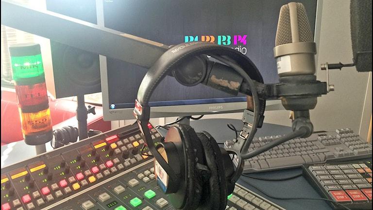 Studiokuva mikrofoni ja kuulokkeet, taustalla tietokone. Foto: Virpi Inkeri/SR