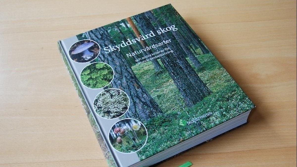 En bild på en stor och tjock bok med en skogsbild på omslaget.