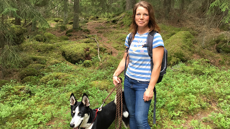 Katja Beck står i en mossig skog med sin svartvita hund i koppel.