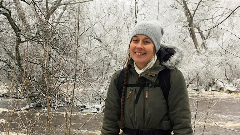 Vintrigt porträtt på kvinna vid strömmande å omgiven av rimfrostiga träd