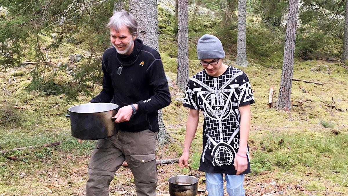 En medelålders man och en kille i 20-årsåldern går i skogen med varsin gryta med vatten.