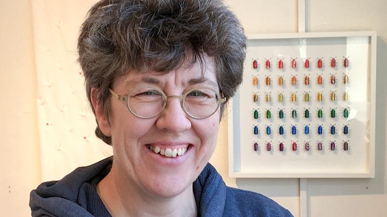 Porträttbild på kvinna med tavla i bakgrunden