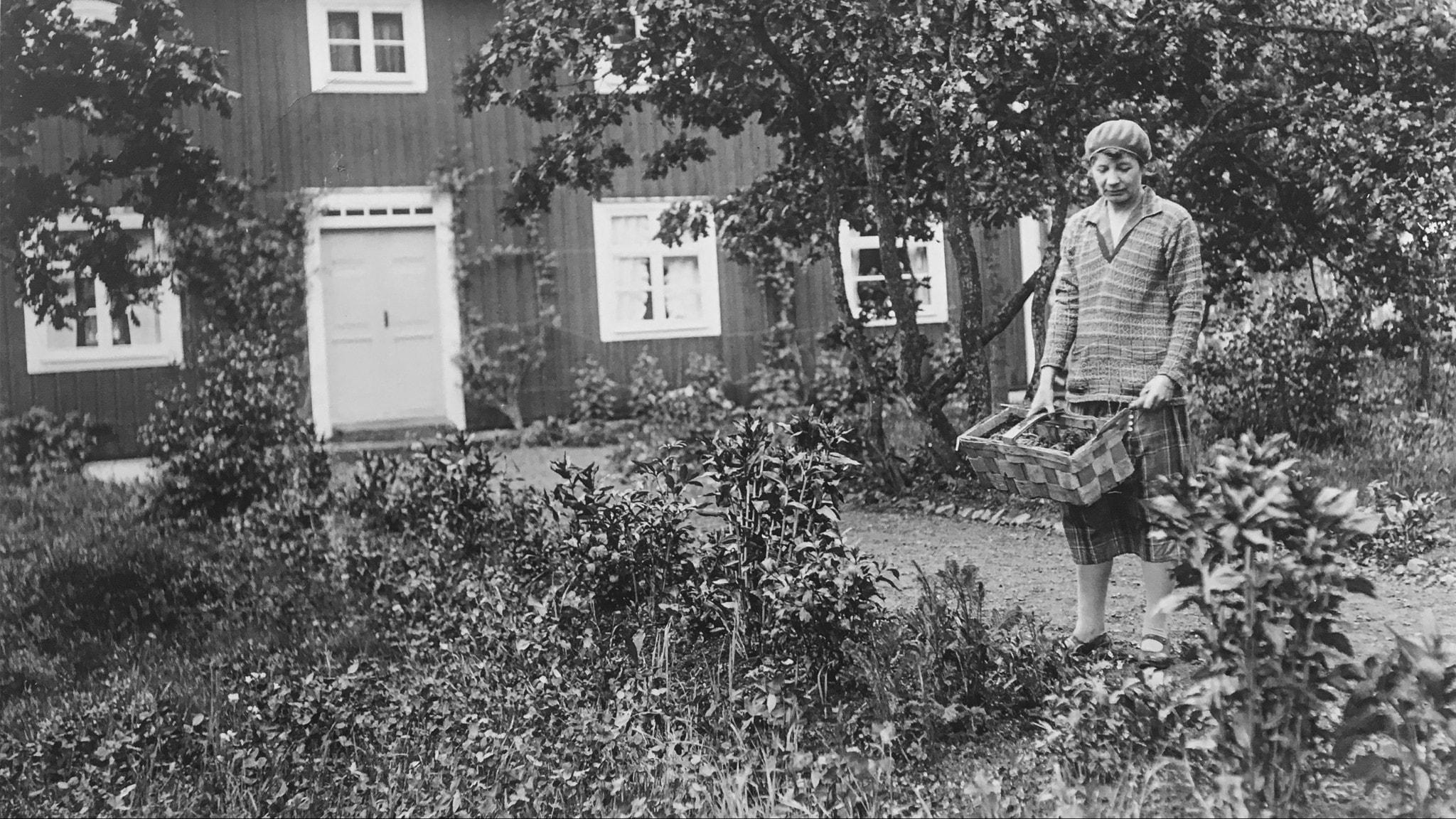 kvinna med korg i trädgård med hus bakom