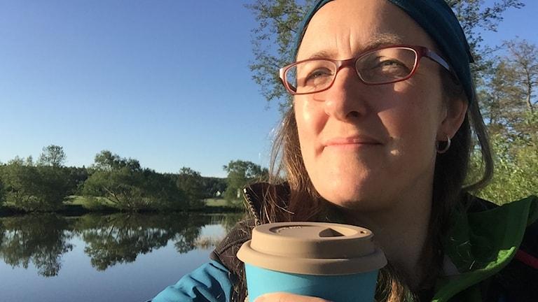 Porträtt på en kvinna som sitter vid en å med en kopp fika
