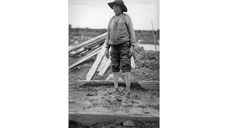 En Jukkasjärvipojke som trampar lerdegen i trätråget. Kallt och arbetsamt arbete som kvinnor och barn utförde. Foto: Ruben E Perhsson 1917. Kiruna bildarkiv, Kiruna kommun.